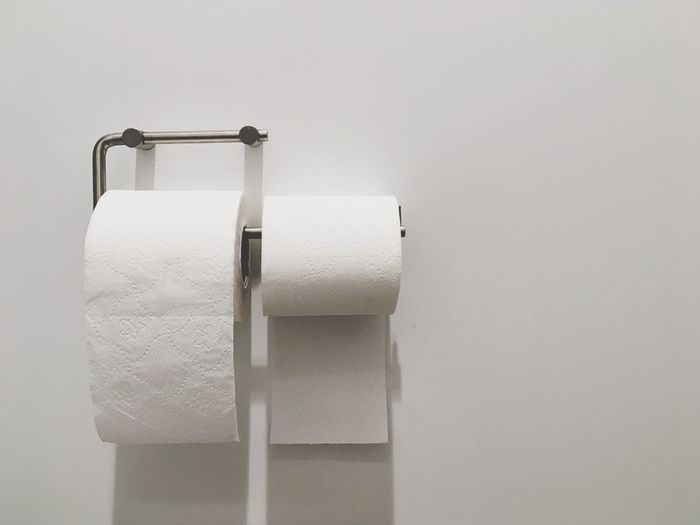 Close-up of toilet papers on white wall