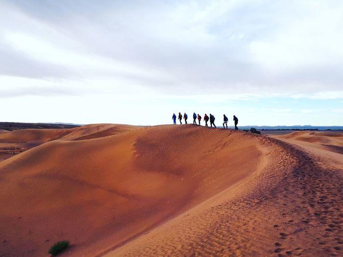 People on sand dune against sky