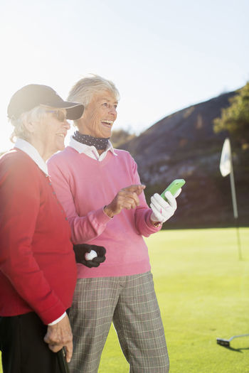 Rear view of man holding woman standing on golf course