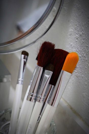 Close-Up Of Make-Up Brushes In Glass Container
