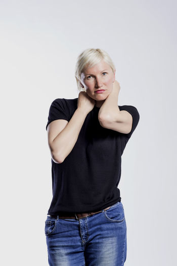 Portrait of a beautiful young blond woman modeling in a studio Studio Shot One Person Front View Casual Clothing Looking At Camera Indoors  Young Adult Portrait Three Quarter Length Standing Young Women Blond Hair White Background Hair Beauty Women Copy Space Cut Out Beautiful Woman Jeans Hairstyle Isolated Females Modelling Model Blonde Girl Lady Looking At Camera Standing