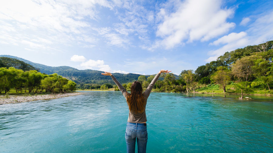 Rear View Of Woman With Arms Raised By River Against Sky