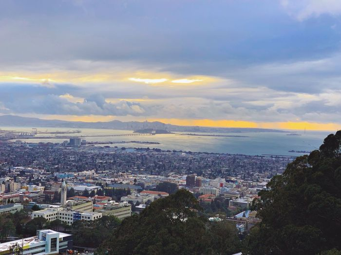 """College View"" A scenic of San Francisco across the UC Berkeley campus. A closer view will reveal the iconic 'Sather Tower' in the left hand corner of the photograph, which is a bell tower, with clocks on its four faces and is a unique center piece on the campus. Clouds Scenics Sunset Dusk Berkeley, CA San Francisco San Francisco Bay City Architecture Building Exterior Sky Built Structure Cloud - Sky Cityscape High Angle View"