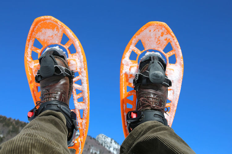 blue sky and a boy with orange snowshoes 2 Hiking People Watching Snowshoe Winter Wintertime Adventure Cold Cold Temperature Equipment Extreme Sports Hike Legs_only Mountain Snow Snow Shoeing Snow Shoes Snowshoe Trip Snowshoeing Snowshoes Sport Two