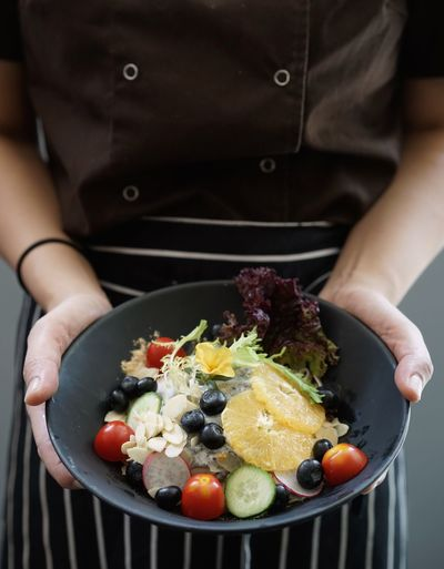 Midsection of chef holding bowl while standing outdoors