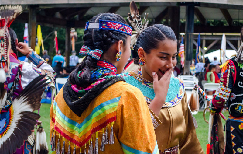 september 3, 2017, American Indian women in traditional clothing, or reglaia, giggle before the dance competition at the Kee-Boon-Mein-Kaa Pow Wow in Dowagiac Michigan USA Beautiful Dowagiac Feathers Horizontal Michigan USA American Indian Clothing Colorful Competition Editorial  Female Girls Hairstyle Happiness Head Piece Leisure Activity Lifestyles Native Amereican People Real People Regalia Smiling Traditional Clothing Women