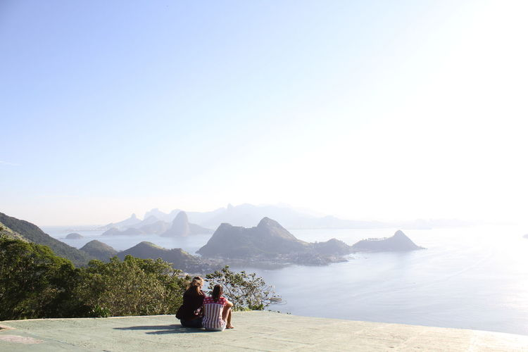 Rear View Of Female Friends Sitting On Observation Point By Sea At Rio De Janeiro