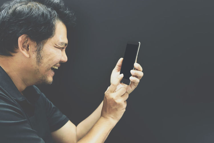 Midsection of man using smart phone against black background