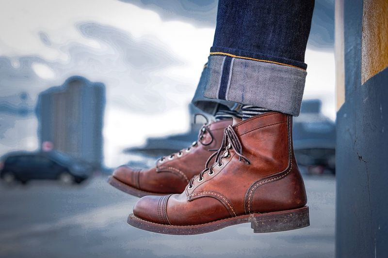 Low section of person wearing leather shoes in city