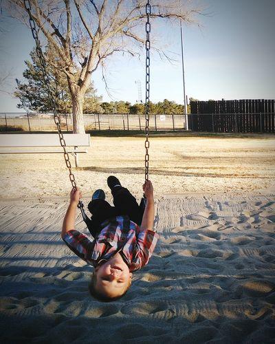 Full length of boy swinging at playground