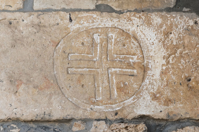 Bar'am, Israel, June 09, 2018 : Decorative carvings over the stone in the course of the church of the Christian Maronites in the abandoned village Kafr Birim in the north of Israel Christian Maronites Church Cross God Jesus Christ Kafr Birim Abandoned Village Arabic Architecture Art Belfry Tower Bible Building Culture Day Heritage History Holy Israel Landmark Monument Old Pry Religion Symbol