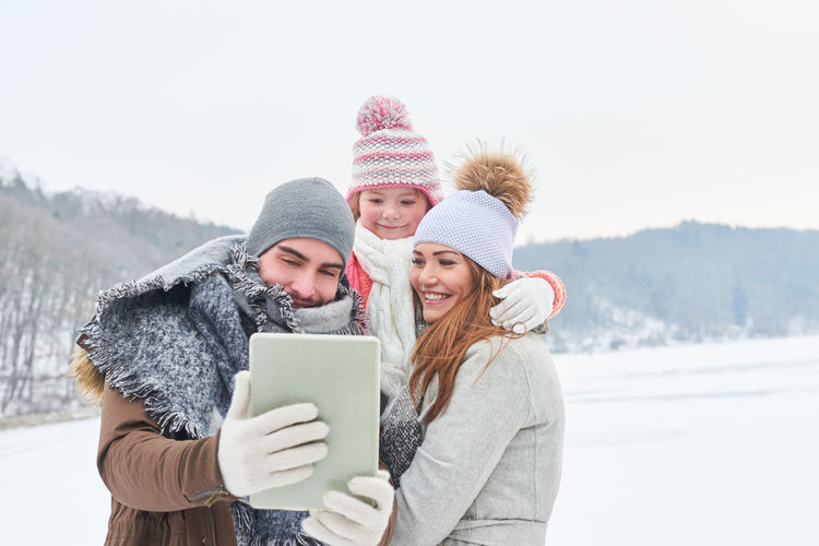 Smiling Family In Warm Clothing Taking Selfie Against Sky During Winter