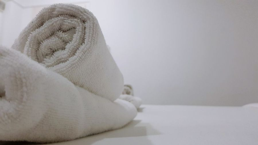 White towels roll on white bed, close up Towel Fabric Cloth Roll Roll Towel Cleaning Bathing White White Background Terry Cloth Wash Cloth Bath Towel No People Winter Indoors  Close-up Wool Day