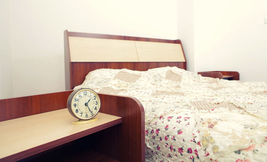 Absence Alarm Clock Bed Bedroom Clock Cozy Domestic Room Electric Lamp Floral Pattern Furniture Home Interior Home Showcase Interior Indoors  Instrument Of Time Night Table No People Pillow Relaxation Side Table Still Life Table Time Wall - Building Feature Wall Clock