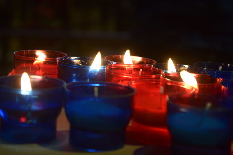 Red and Blue candles in the Notre Dame Belief Built Structure Burning Candle Close-up Dark Fire Fire - Natural Phenomenon Flame Focus On Foreground Glass Glowing Heat - Temperature Illuminated Indoors  Nature No People Religion Selective Focus Spirituality Table Tea Light