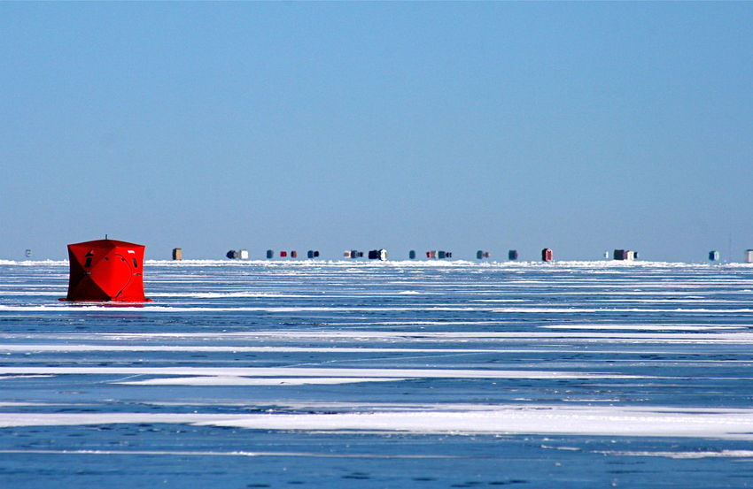 Ice fishing huts on a frozen lake Clear Day Cold Winter ❄⛄ Day Frozen Lake Ice Fishing Huts Red Hut Snow And Ice  Traveling Lake Simcoe Light Relections On Ice