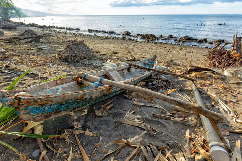 A traditional boat on a beach in Maumere on the island of East Nusa Tenggara in Indonesia. INDONESIA Palm Swimming Tourist Tourist Attraction  Travel Beach Boat Clouds Destination East Nusa Tenggara Explore Fishing Flores Lanscape Maumere Mountain Nature No People Ocean Outdoors Swim Tourism Traditonal Tropical