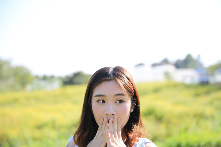Surprised young woman covering mouth while looking away against sky