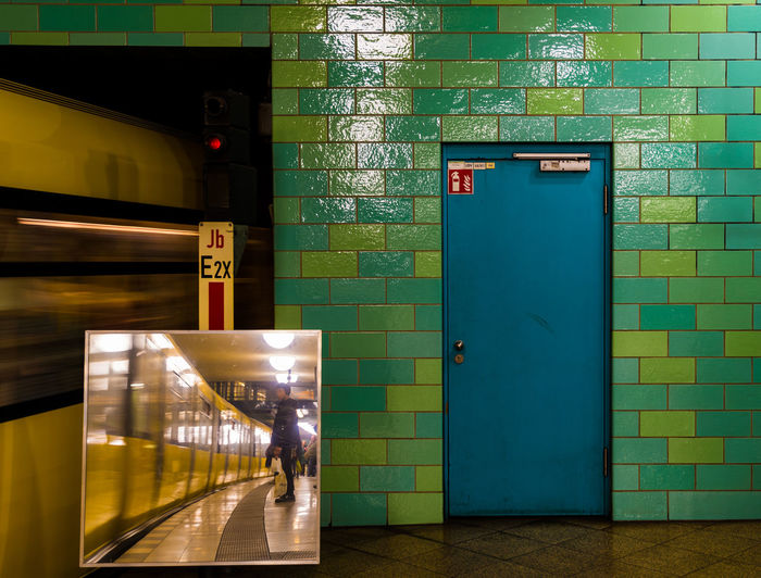 Reflection of man standing in subway station against closed door