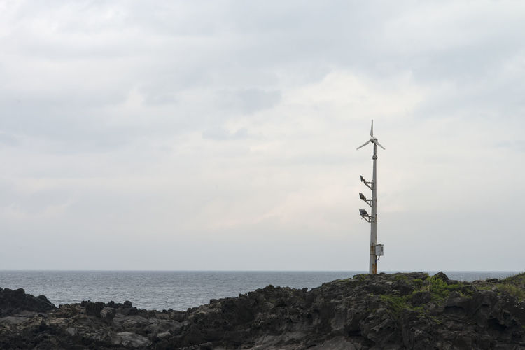 cloudy seaside view of Eoyeongmaeul in Jeju Island, South Korea Beauty In Nature Cloud - Sky Cloudy Day Eoyeongmaeul Horizon Over Water Industrial Windmill JEJU ISLAND  Nature No People Outdoors Rainy Day Rock - Object Scenics Sea Seaside Sky Tranquil Scene Tranquility Water Wind Power Wind Turbine Windmill