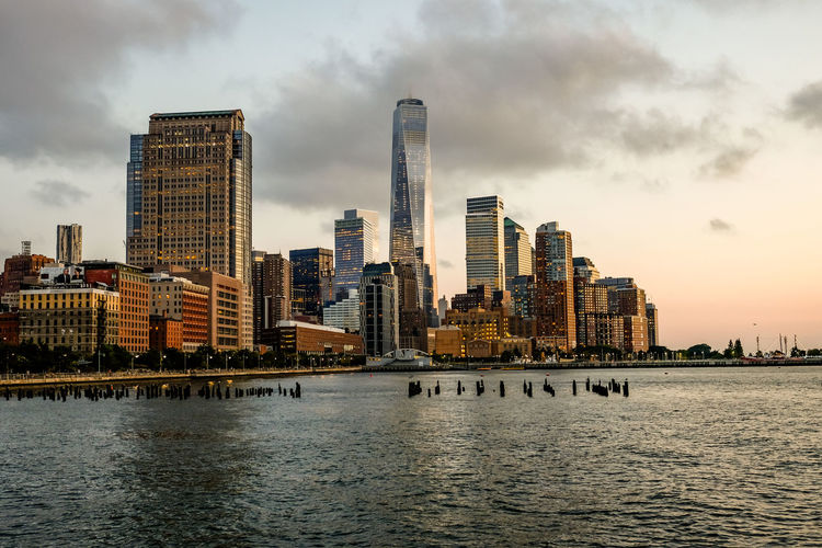 East river with one world trade center in manhattan against sky