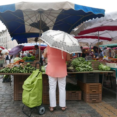 Rear View Of Woman Buying Vegetables In Market During Rainy Season