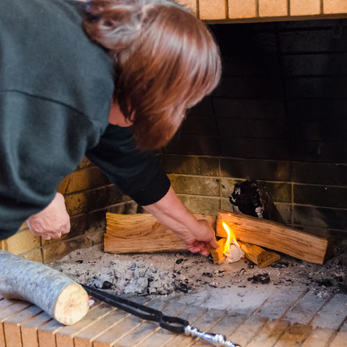 Rear view of woman burning wood at fireplace
