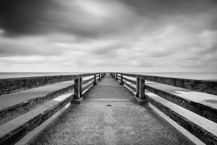 Footbridge leading towards sea against sky