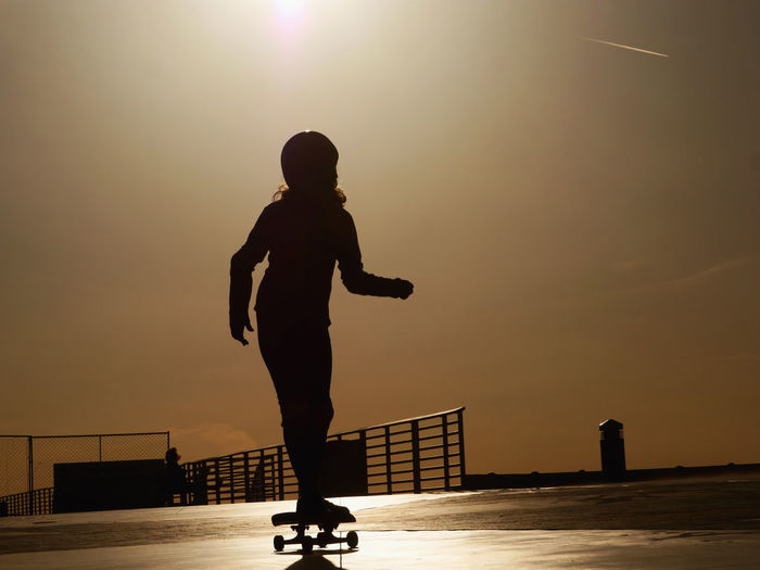 Silhouette Woman Skateboarding On Footpath Against Sky During Sunset