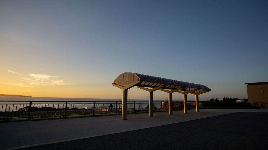 Lifeguard hut on road by sea against clear sky