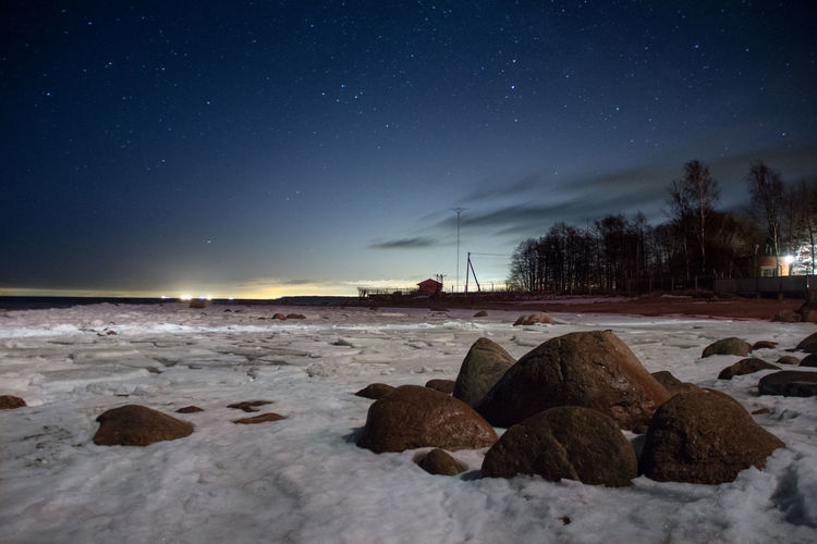 Scenic view of rocks amidst snow at beach against sky during night