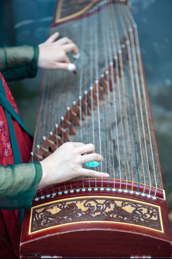 playing guzheng Adult Arts Culture And Entertainment Day Finger Focus On Foreground Guzheng Hand Holding Human Body Part Human Hand Indoors  Leisure Activity Midsection Music Musical Equipment Musical Instrument One Person Playing Real People Skill  Women