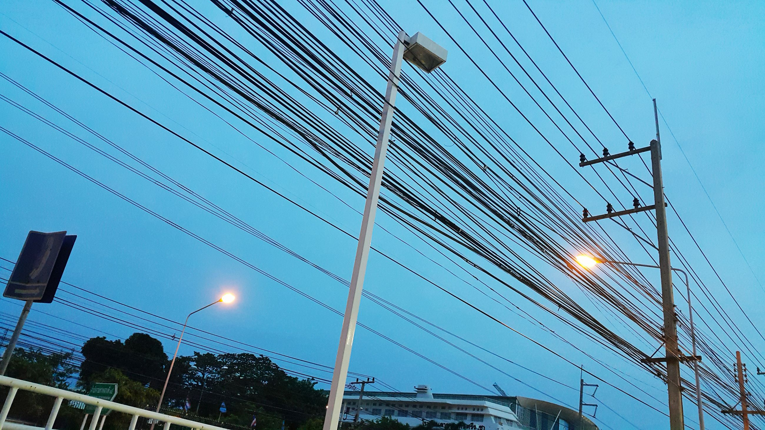 low angle view, power line, electricity, cable, power supply, connection, electricity pylon, sky, technology, blue, fuel and power generation, transportation, street light, built structure, power cable, lighting equipment, day, architecture, outdoors, complexity