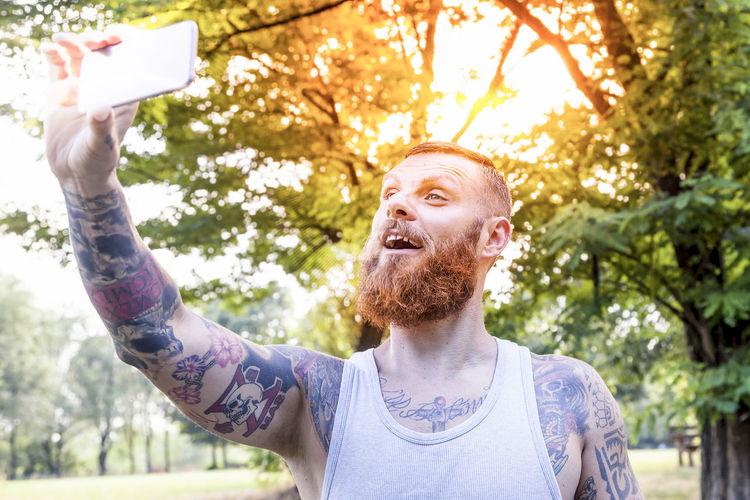 Man taking selfie on mobile phone against trees