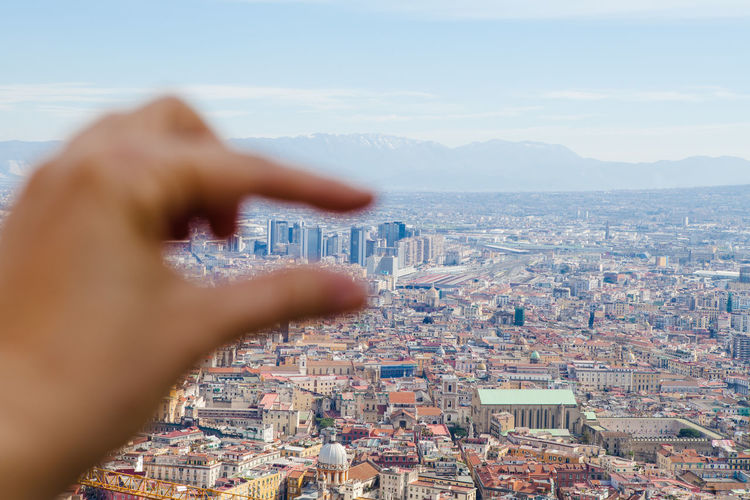 Optical illusion of hand reaching city