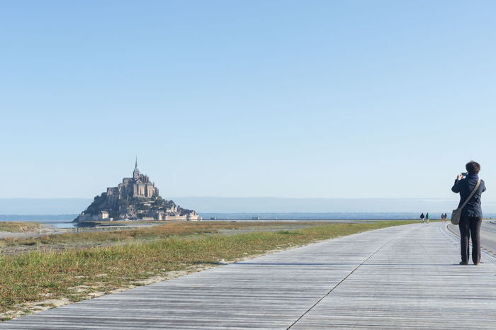 Adult Architecture Building Exterior Built Structure Clear Sky Day France Full Length Mont Saint Michel Montsaintmichel Mount Saint Michel Mountsaintmichel Nature Normandie Normandy One Person Outdoors Real People Rear View Scenics Sea Sky Travel Destinations Water