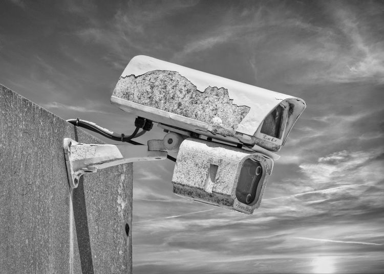Low angle view of a security camera against sky