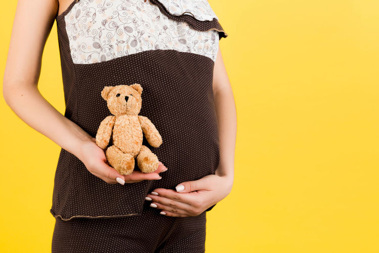 Midsection of girl holding toy against orange background