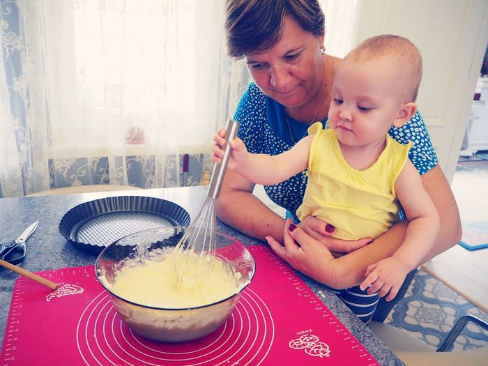 Grandmother Holding Cute Baby Boy While Mixing Food In Bowl With Wire Whisk