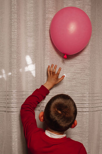 Rear view of boy with balloons