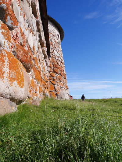 Russia Solovki Solovetskie Ostrova Architecture Grass Built Structure Field Day Nature Sky History Outdoors Growth Landscape Beauty In Nature Building Exterior Ancient Civilization Stone Wall Stone Wall Church Monastery Tower Grass Monk