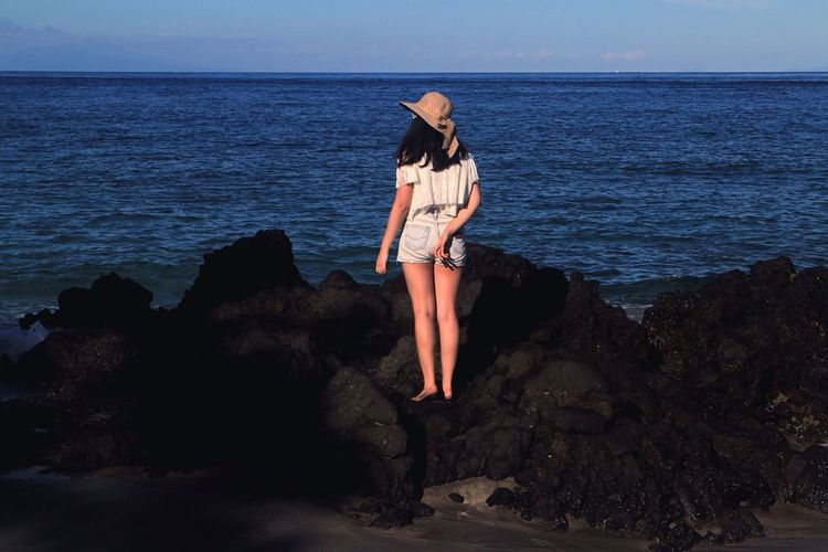 Rear View Full Length Of Woman Standing On Rocky Shore