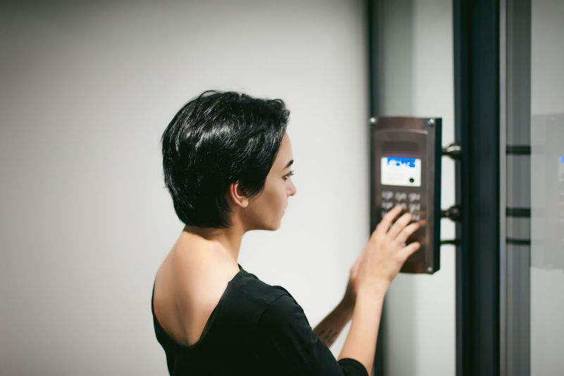 Close-Up Of Young Woman Using Digital Door Lock