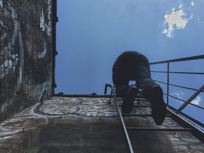 Low Angle View Of Man Climbing Ladder On Building Against Sky