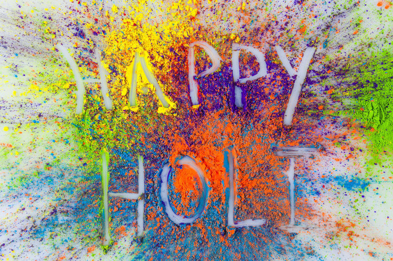 Happy Holi written on vibrant Holi powder Holi Festival Holi Festival Of Colours Blue Close-up Colorful Day Dye Holi Holi Powder Multi Colored No People Outdoors Paint Top View Yellow
