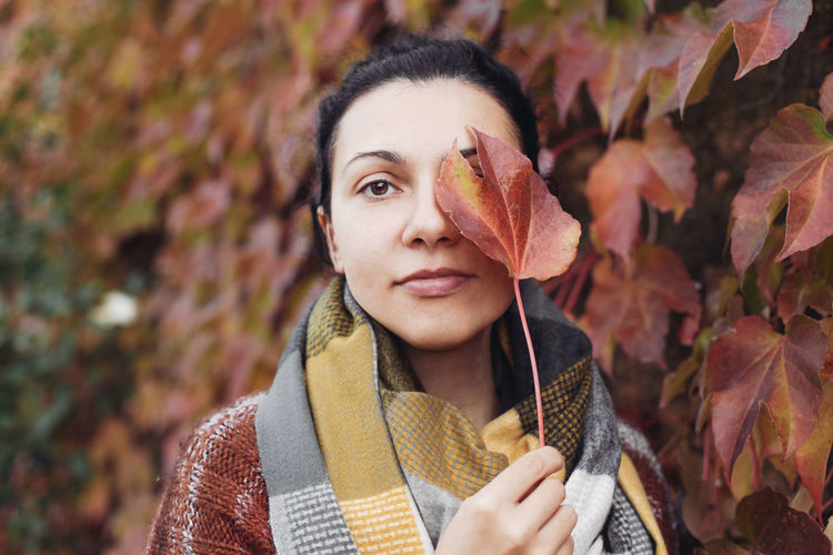 Portrait of young woman with leaves during autumn