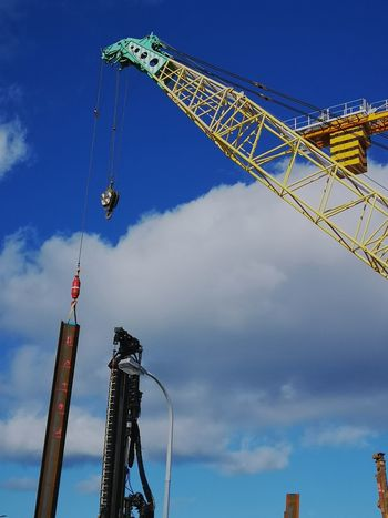 Crane arm extended out EyeEmNewHere City Industry Crane - Construction Machinery Flag Sky Architecture Built Structure Tall - High Construction Scaffolding Construction Site Crane Construction Equipment