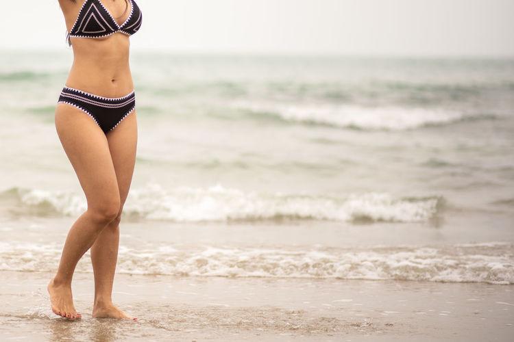 Beach Sea Land Water Swimwear Clothing One Person Motion Leisure Activity Wave Bikini Lifestyles Day Focus On Foreground Women barefoot Standing Nature Outdoors Bikini Bottom