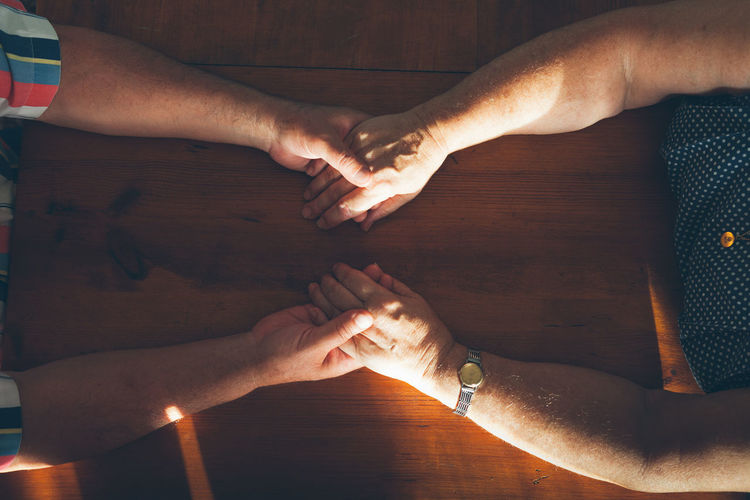 Directly above shot of couple holding hands over table