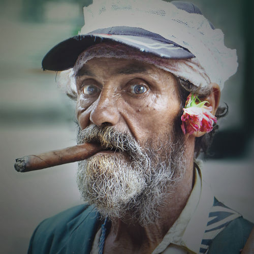 Portrait of senior man in cap smoking cigar